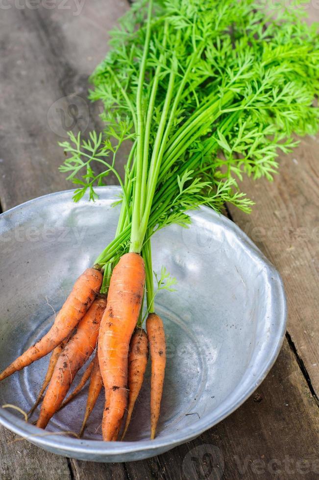 carota fresca non lavata in ciotola su vecchio backgound di legno foto