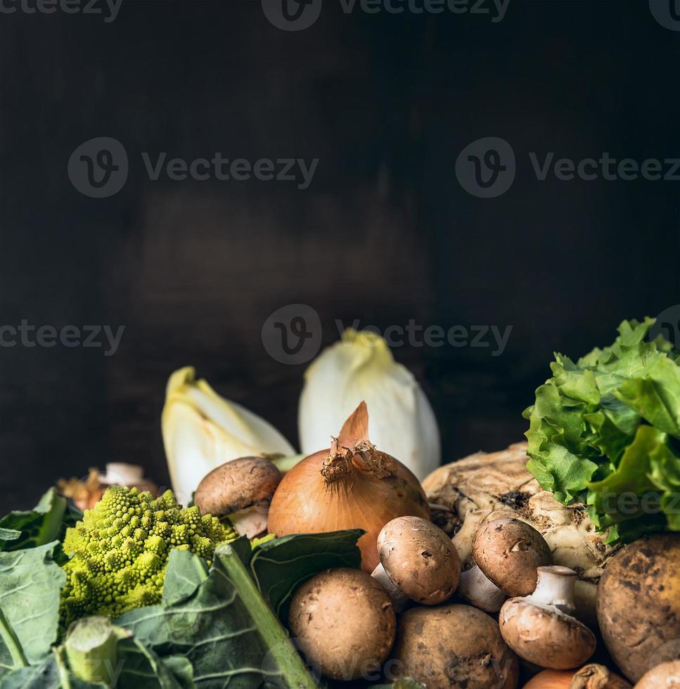 condire le verdure per cucinare su sfondo scuro foto