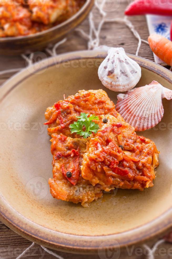 pesce di tipo greco con verdure e salsa di pomodoro foto