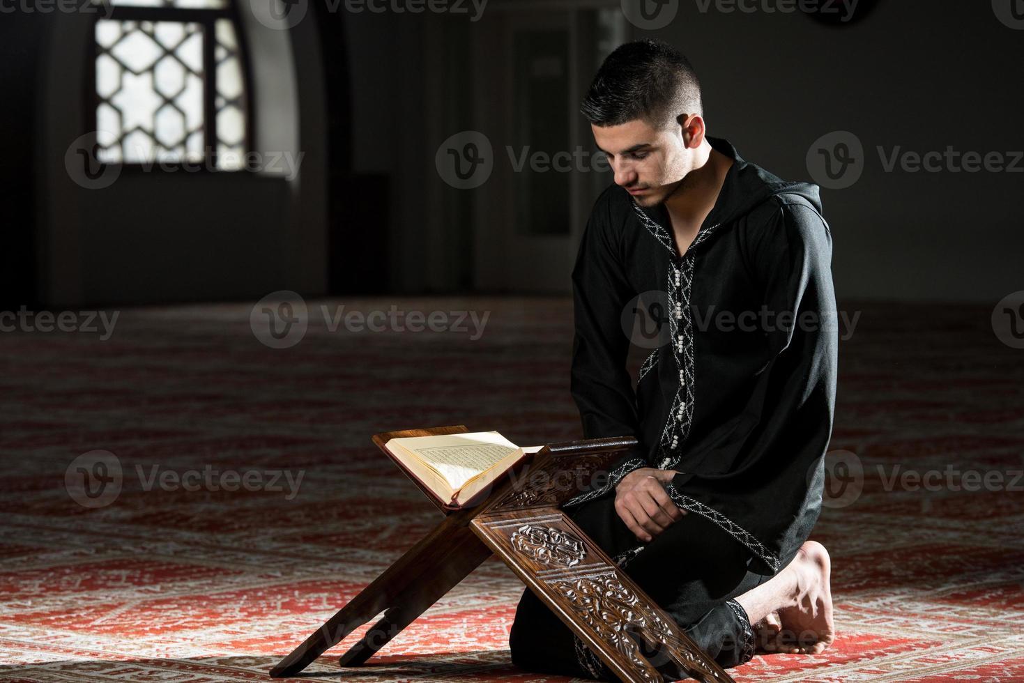 giovane musulmano che legge il Corano foto