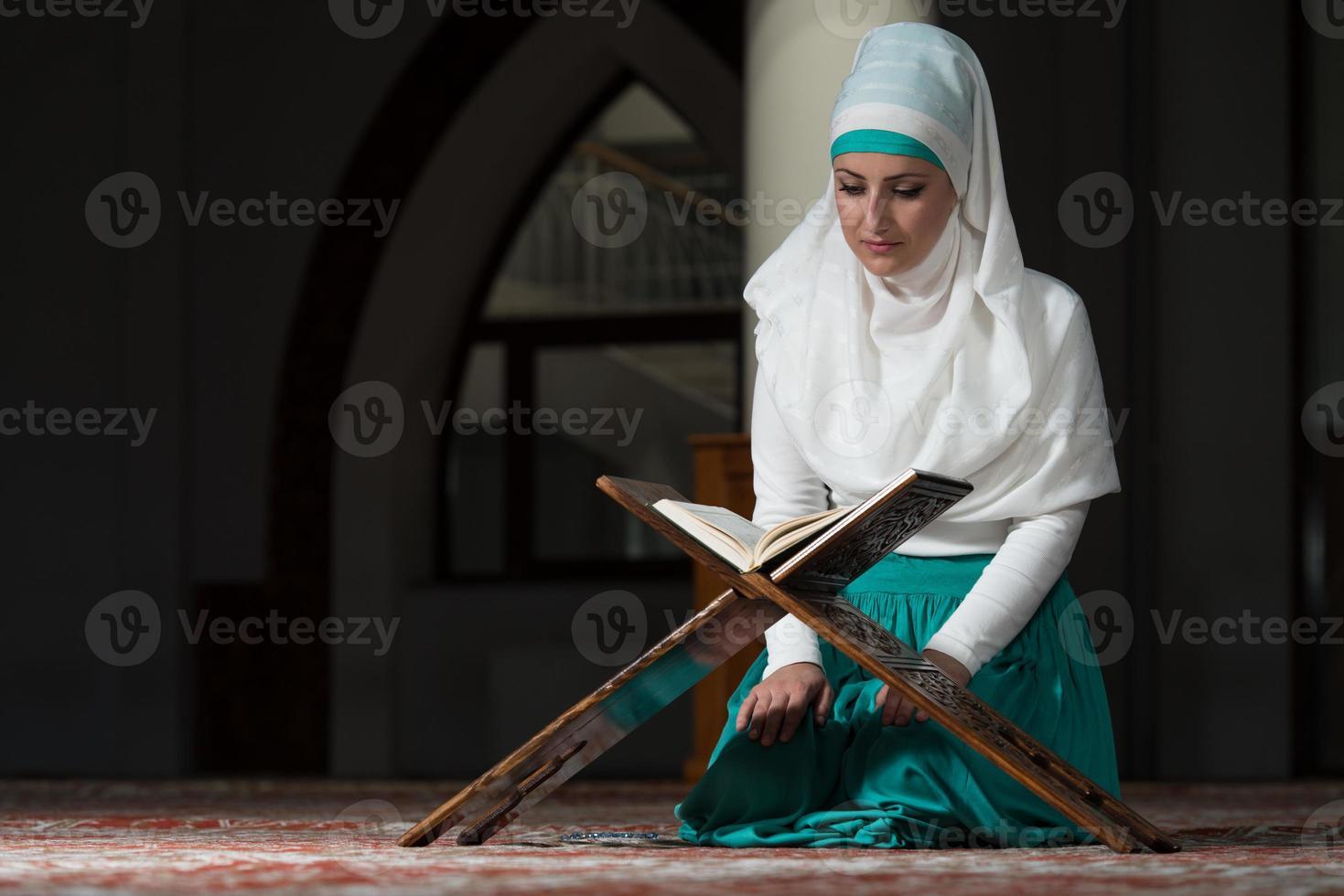 donna musulmana che legge il Corano foto