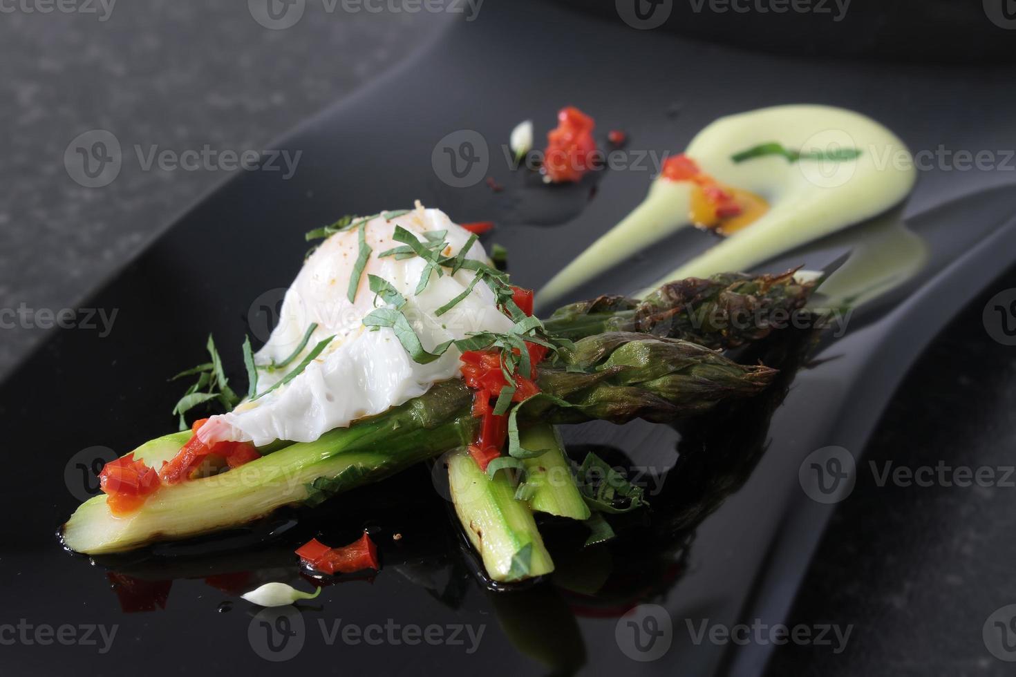 chef preparare asparagi con uova di quial in camicia foto
