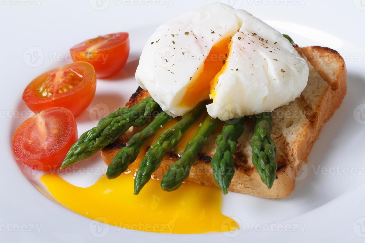 toast con asparagi, uovo in camicia e pomodoro primo piano foto