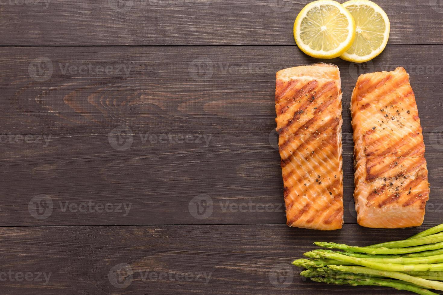 salmone alla griglia con limone, asparagi su fondo in legno foto
