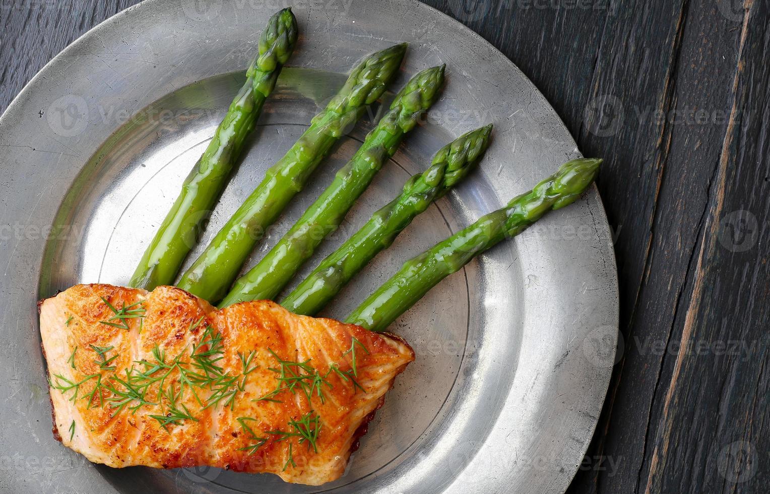 filetto di salmone con asparagi sul vecchio piatto di latta foto