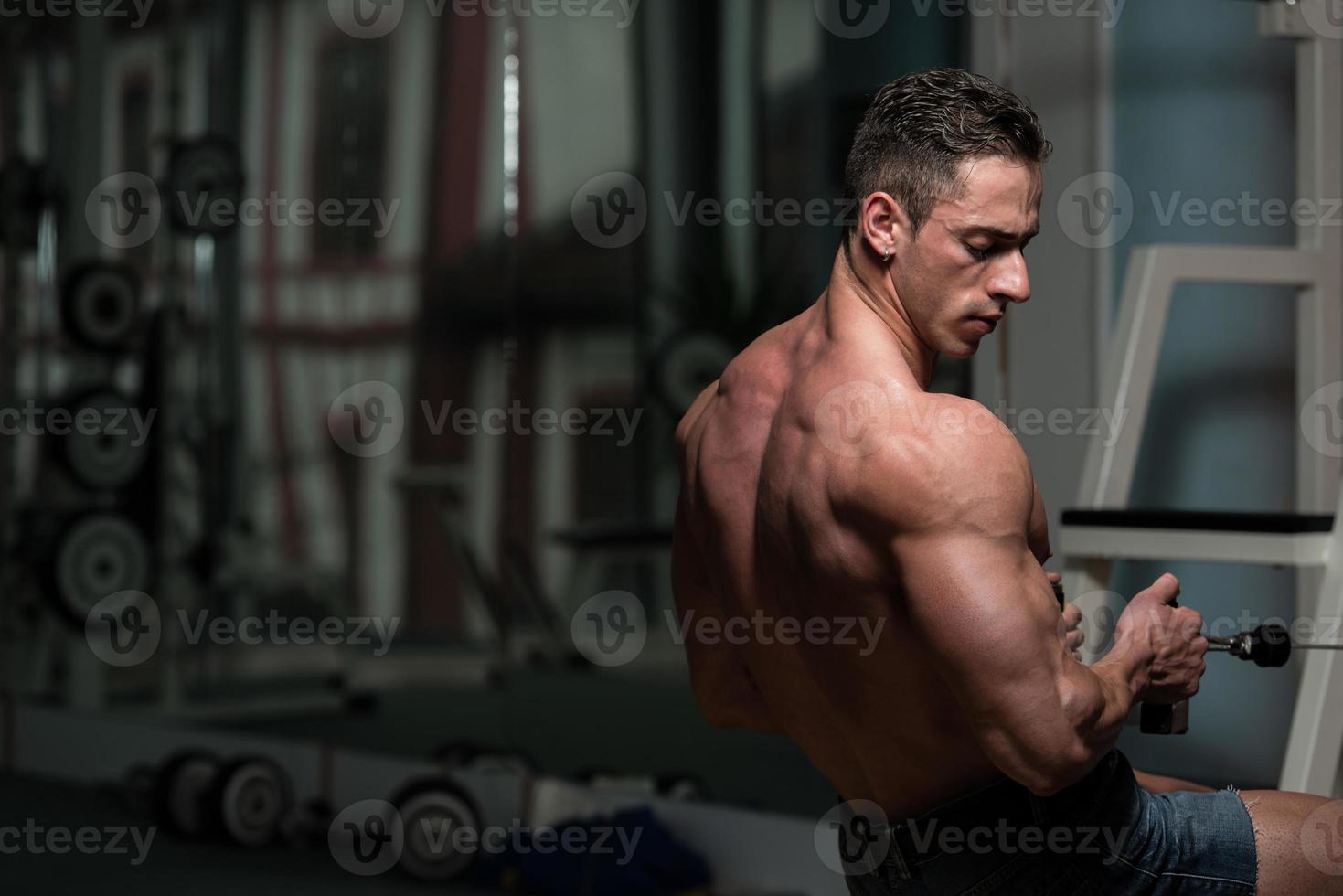 giovane maschio facendo esercizi di schiena in palestra foto