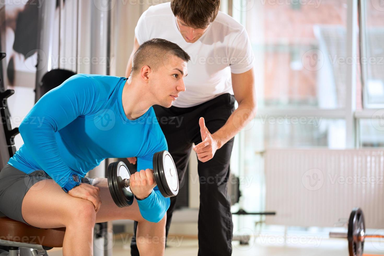 uomo che fa sollevamento pesi con trainer foto