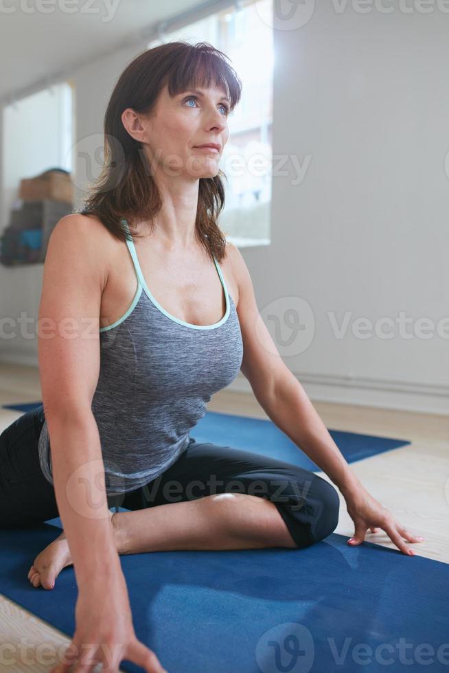 donna adatta che fa yoga in palestra foto