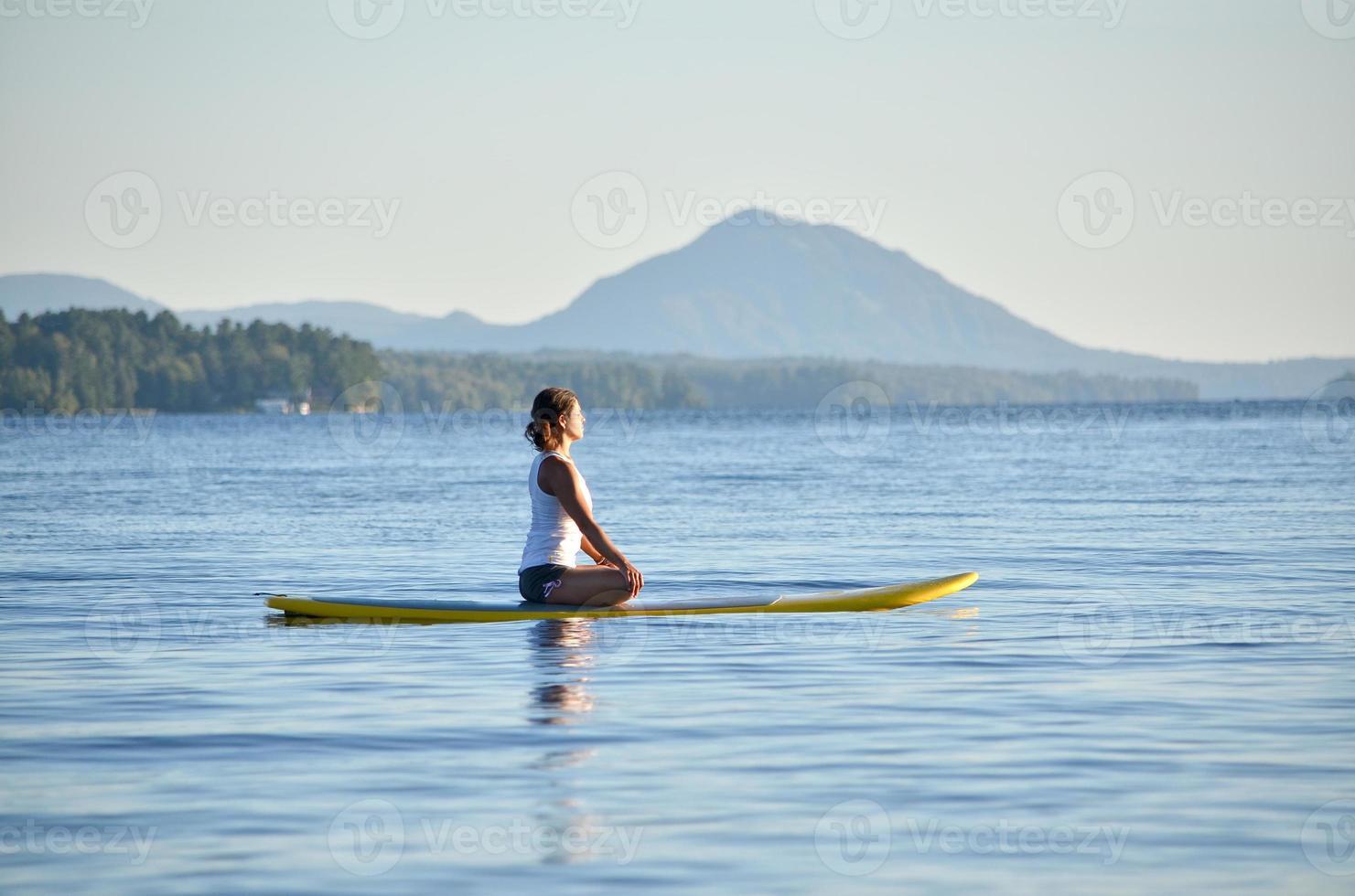 donna su stand up paddleboard, yoga foto