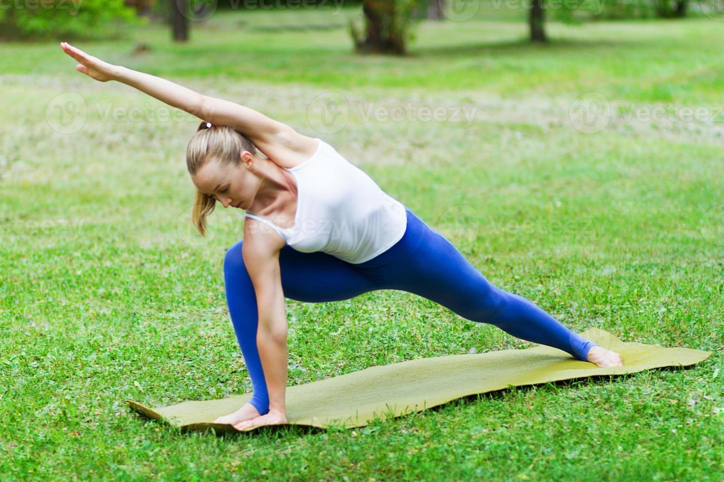 donna che fa yoga sull'erba foto