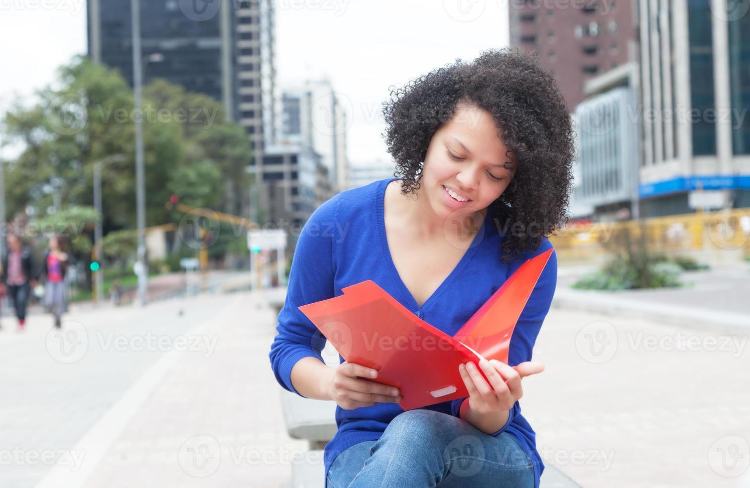 studente latino con documento di lettura dei capelli ricci in città foto