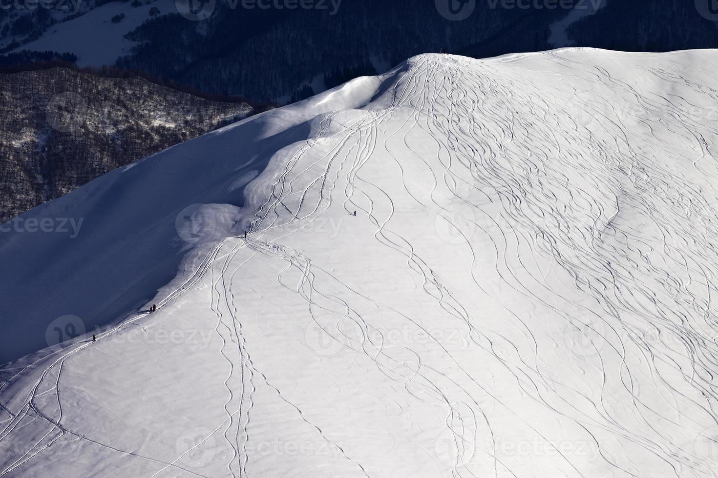 vista dall'alto sul pendio fuori pista con snowboarder e sciatori foto