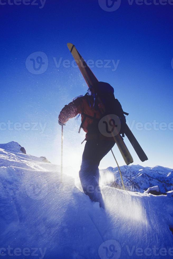 persona che cammina nella neve con gli sci foto