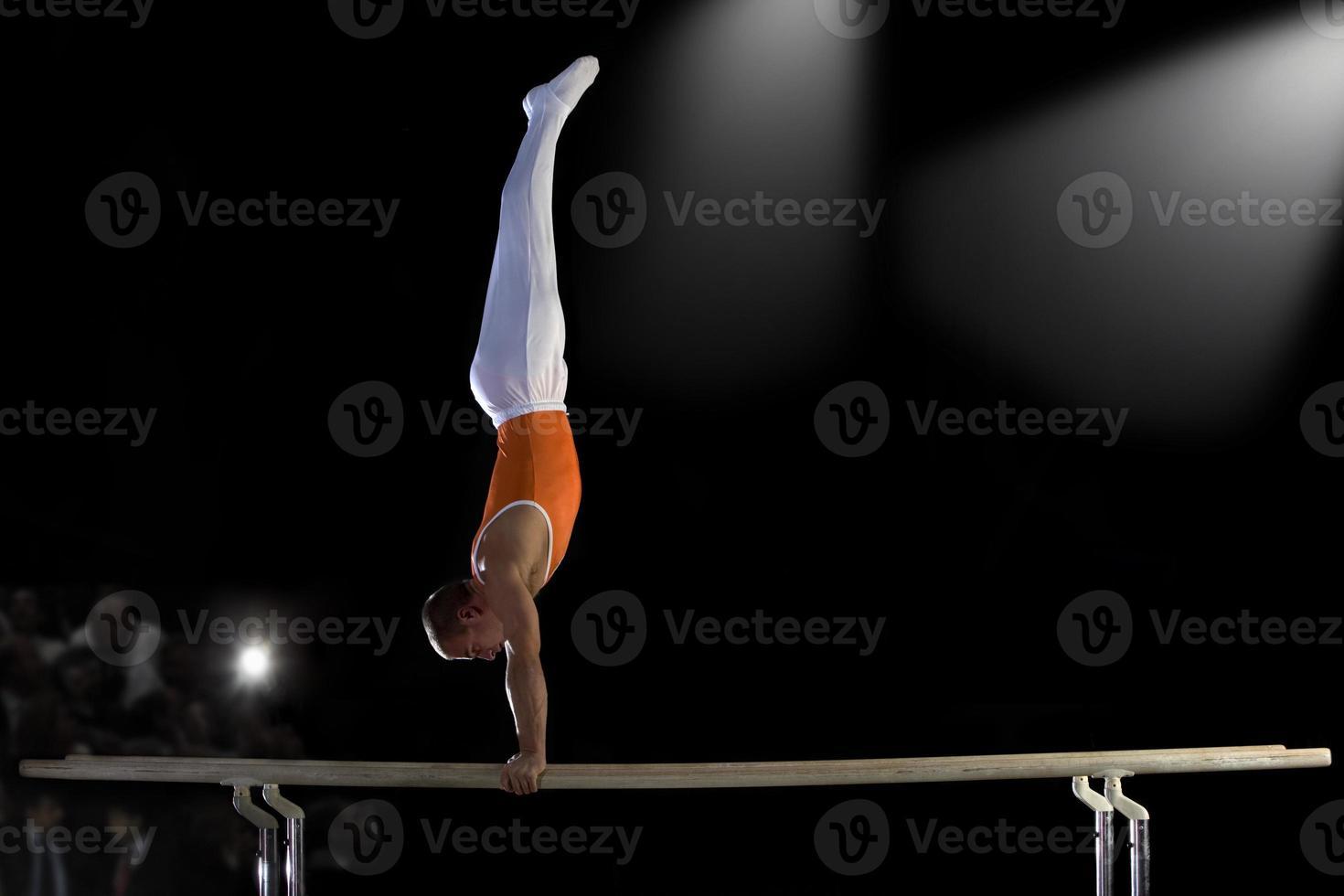 ginnasta maschio eseguendo verticale su barre parallele, vista laterale foto
