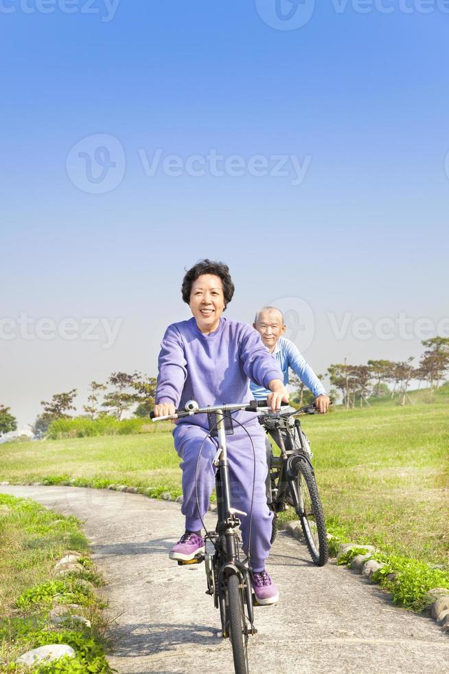 gli anziani coppia in bicicletta nel parco foto
