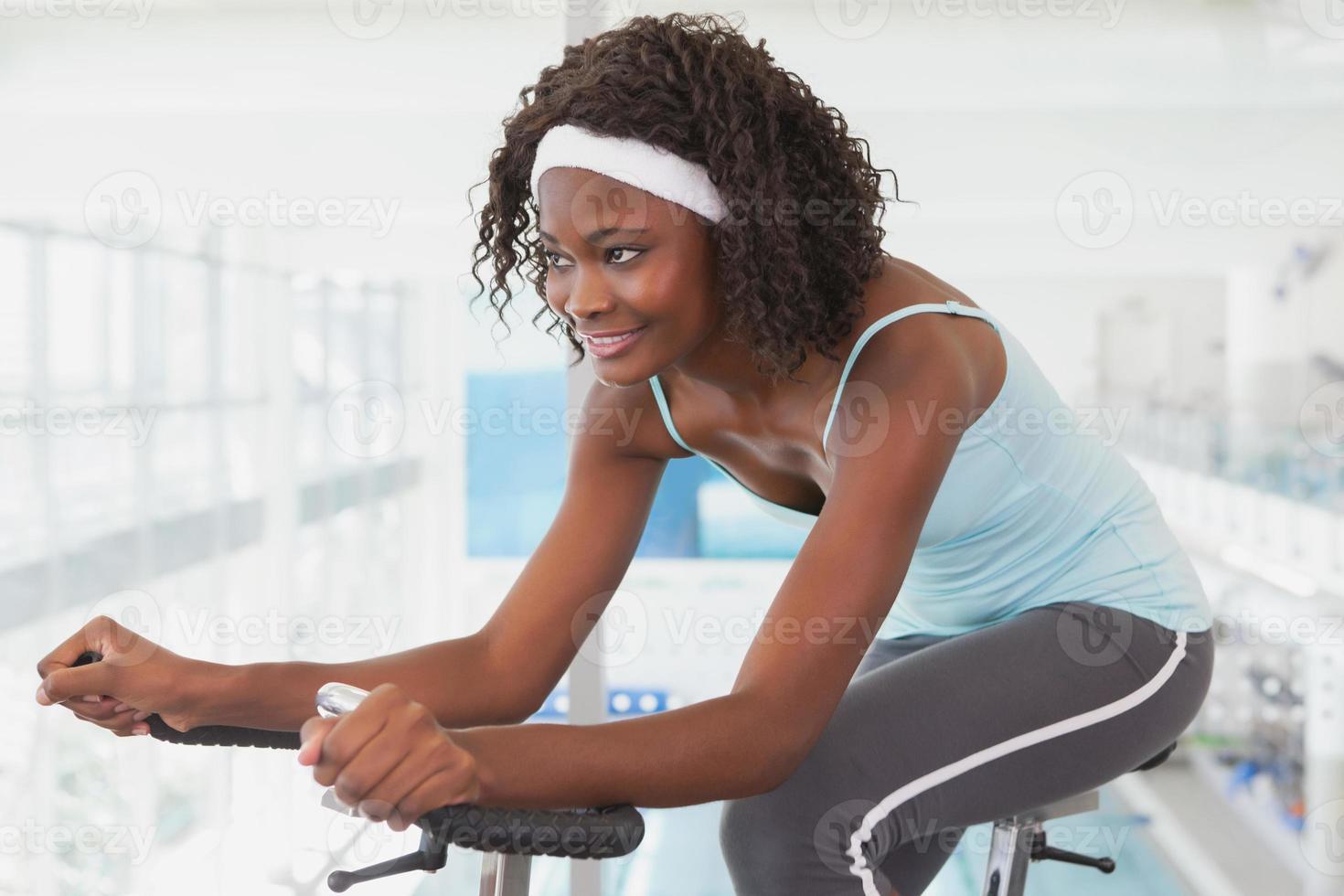 donna adatta che lavora sulla cyclette foto
