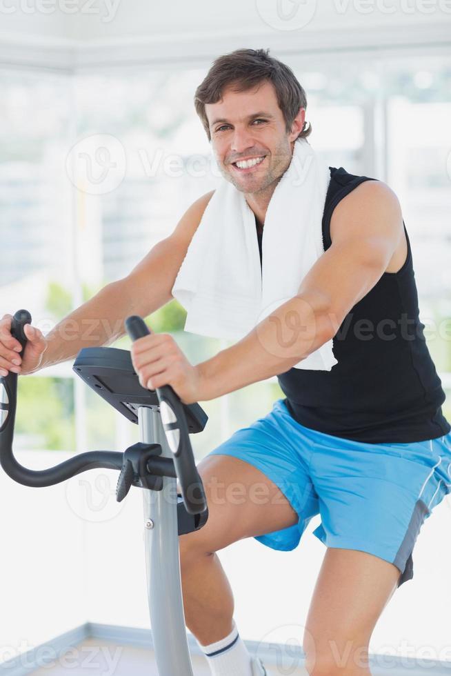 uomo sorridente che lavora alla classe di spinning in palestra luminosa foto