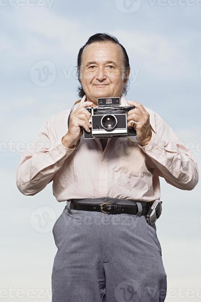 uomo che tiene una macchina fotografica foto