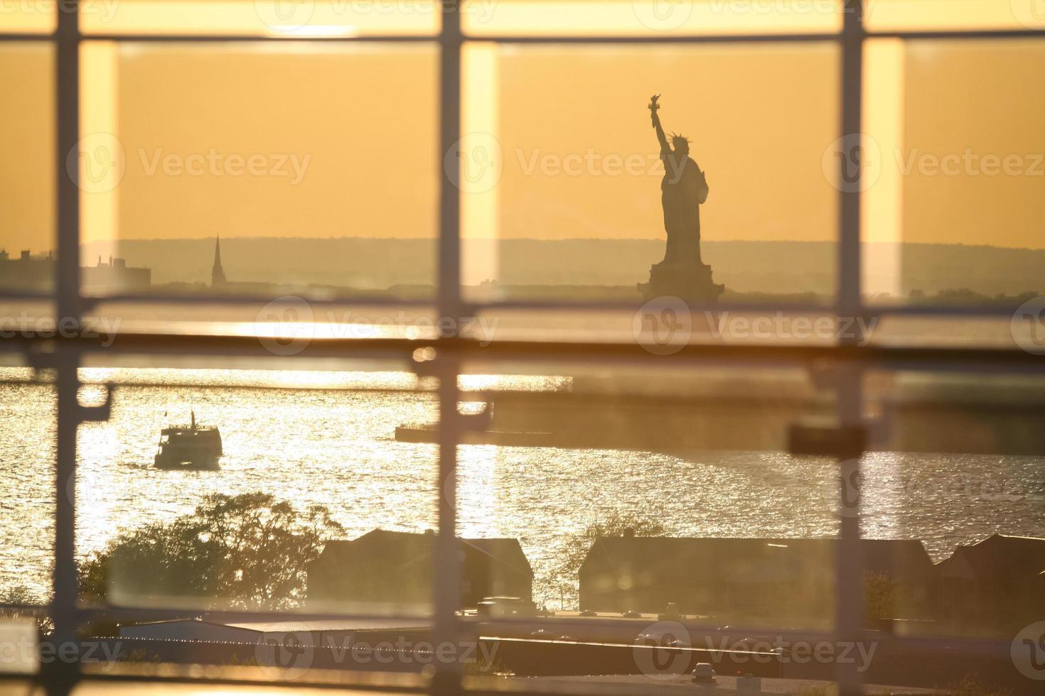 vista della statua della libertà attraverso la recinzione di vetro foto