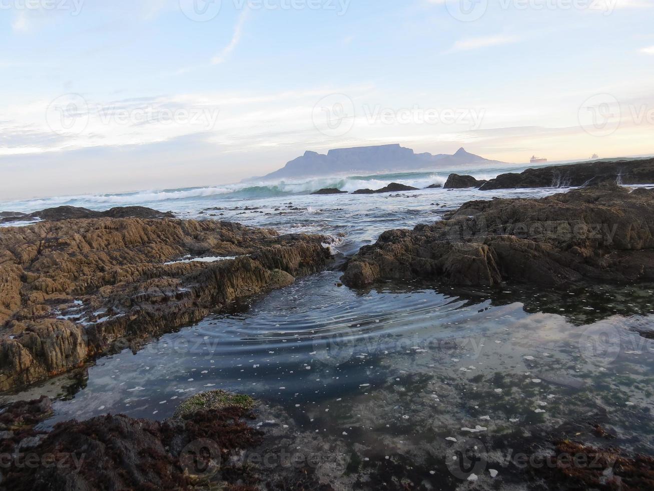 acqua che si increspa attraverso le rocce in riva al mare foto