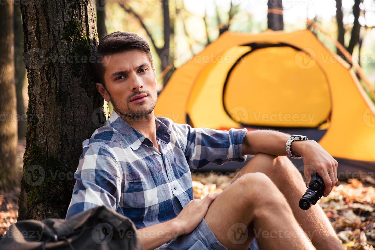 uomo che riposa vicino alla tenda nella foresta foto