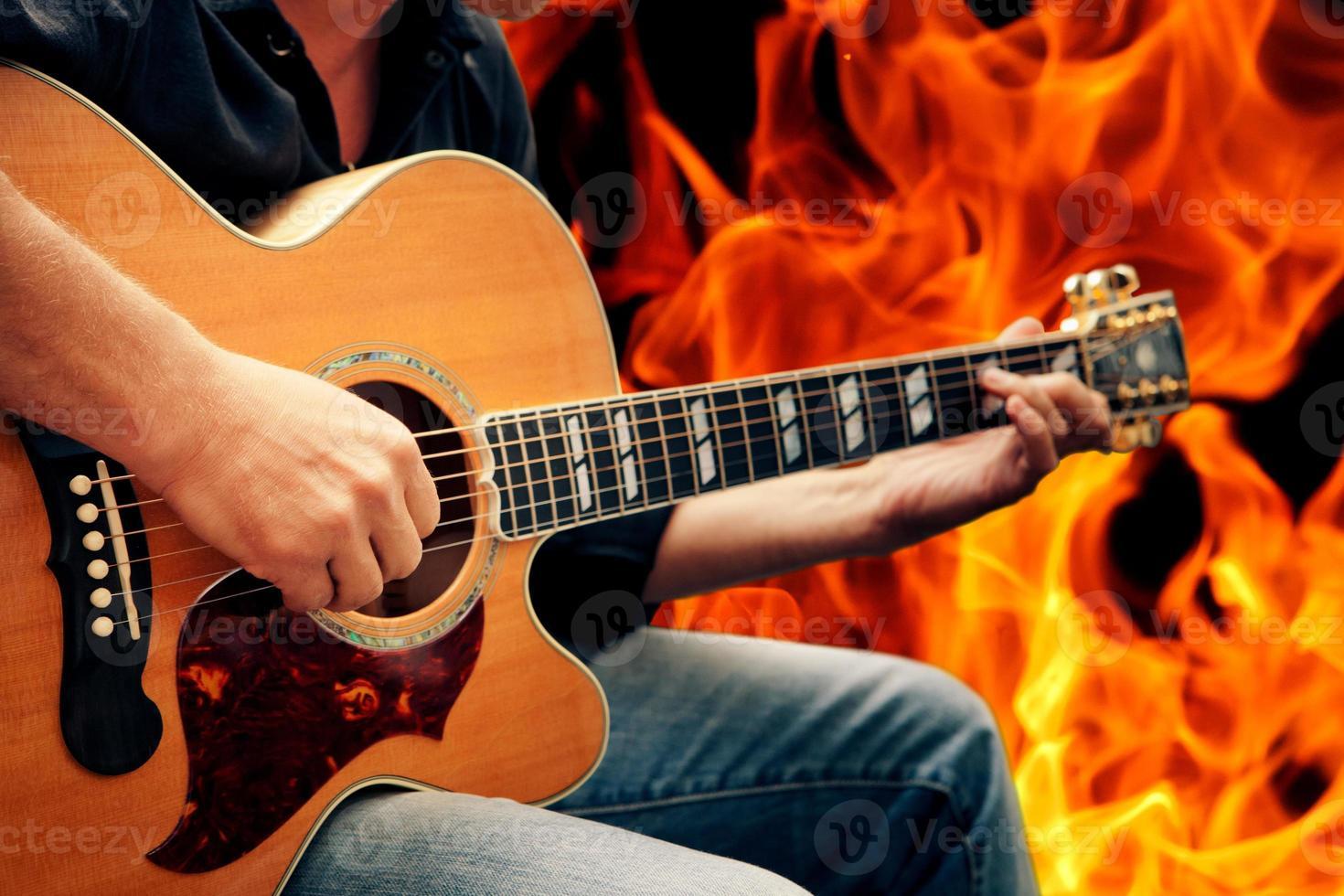 uomo che suona la chitarra contro il fuoco foto