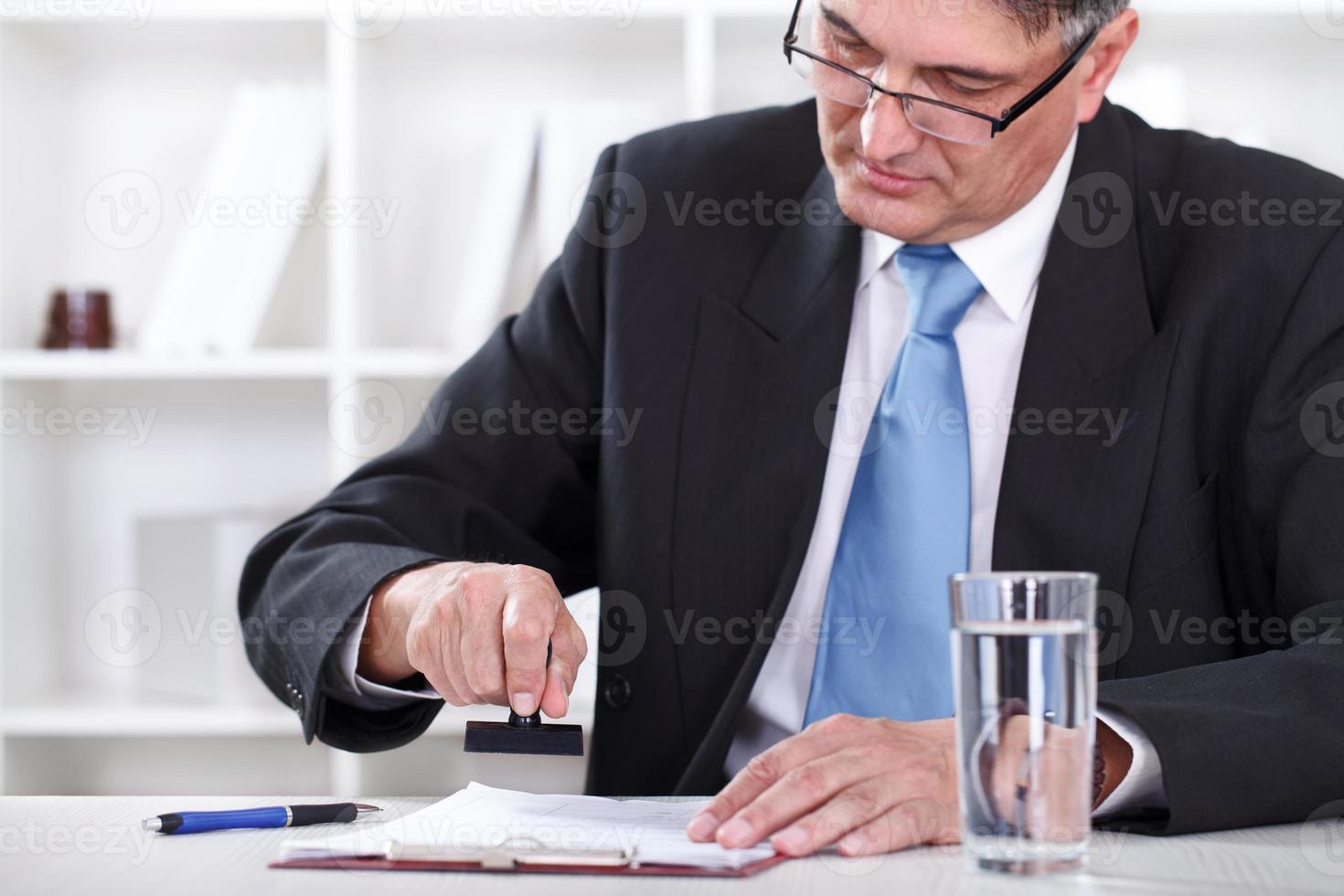 uomo d'affari che timbra il documento, approva il contratto foto