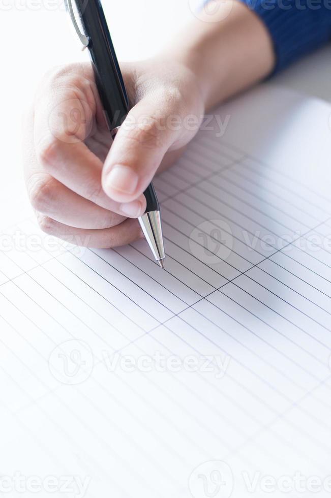 mani femminili con scrittura a penna su carta foto
