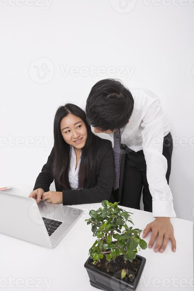 persone di affari che discutono sopra il computer portatile alla scrivania foto