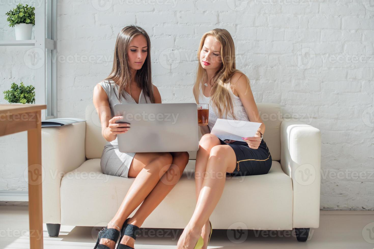 discussione amichevole di due donne d'affari durante la pausa in ufficio utilizzando foto