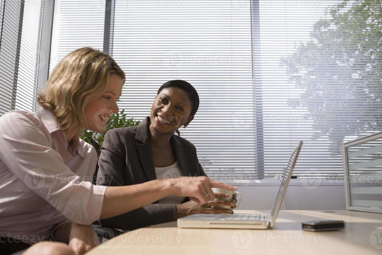 donne di affari che per mezzo insieme del computer portatile foto