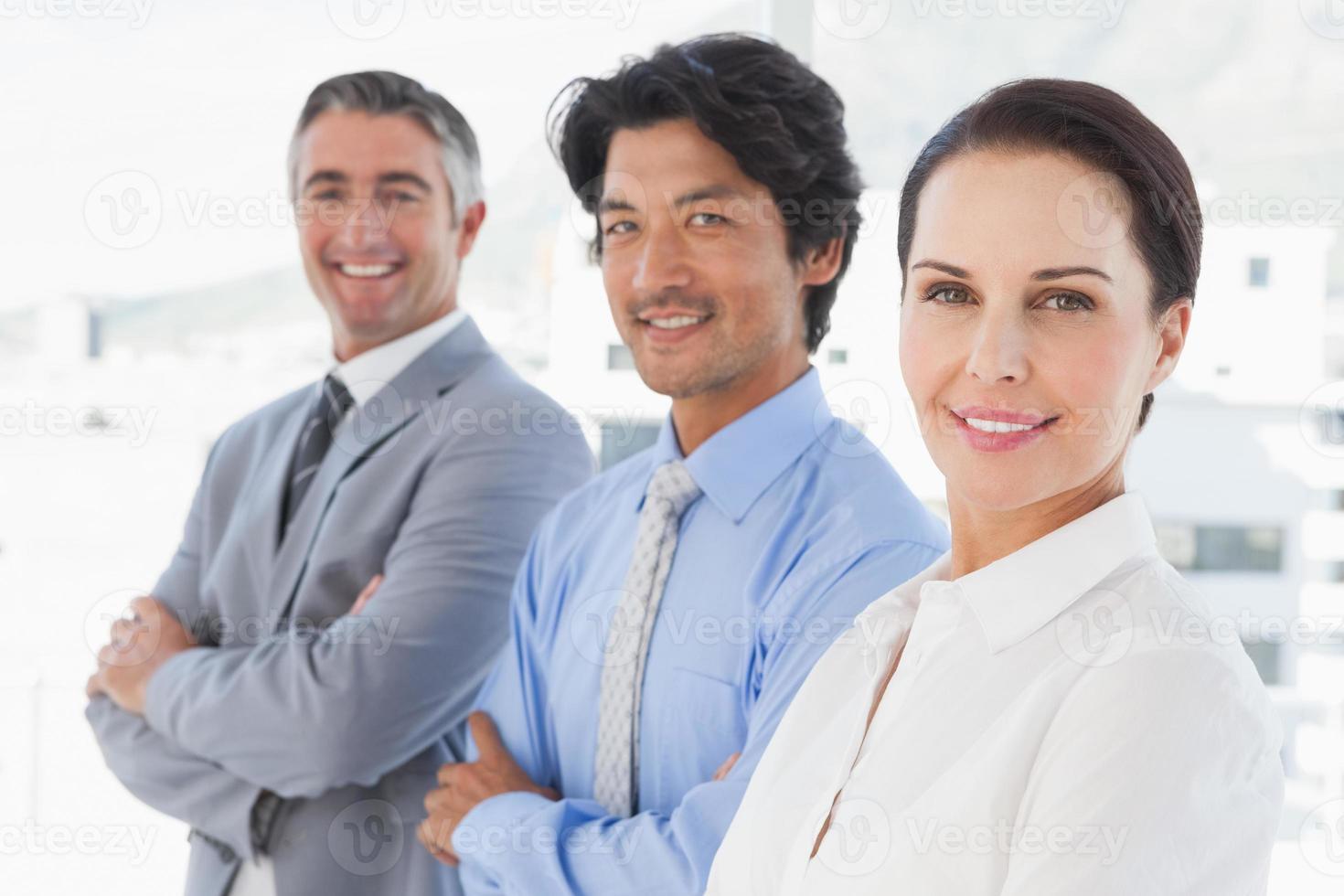 colleghi di lavoro sorridenti che stanno insieme foto