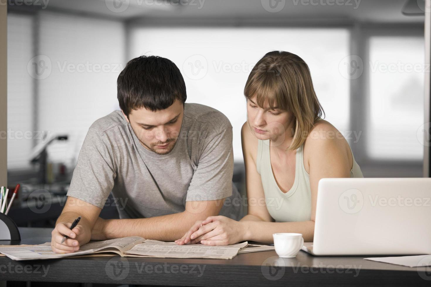 coppia leggendo il giornale insieme al bancone foto