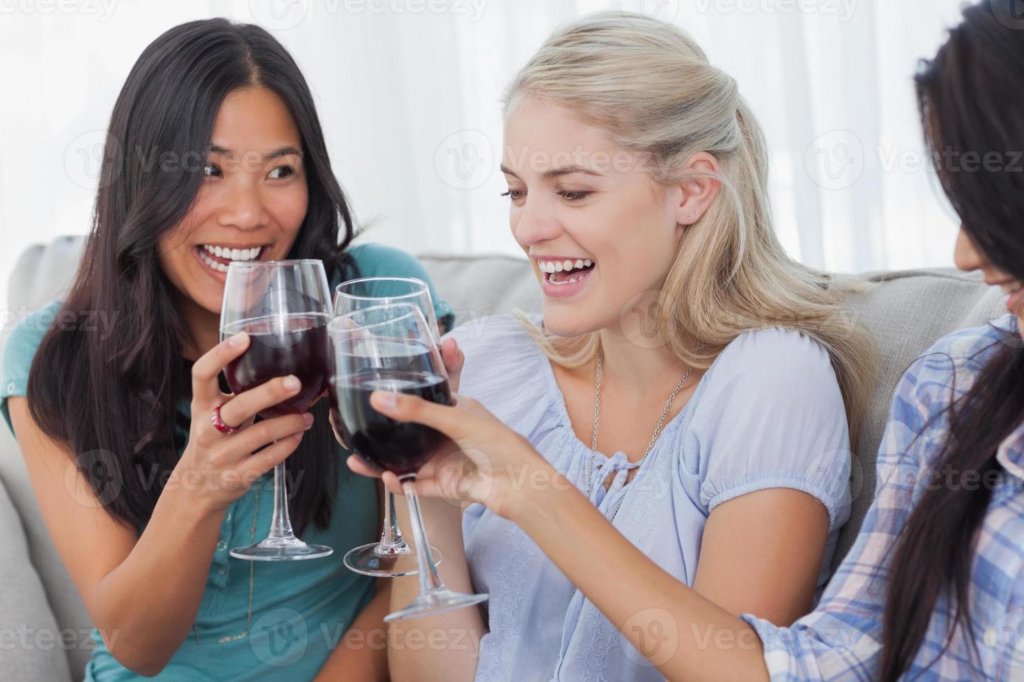 amici felici che tostano insieme con il vino rosso foto