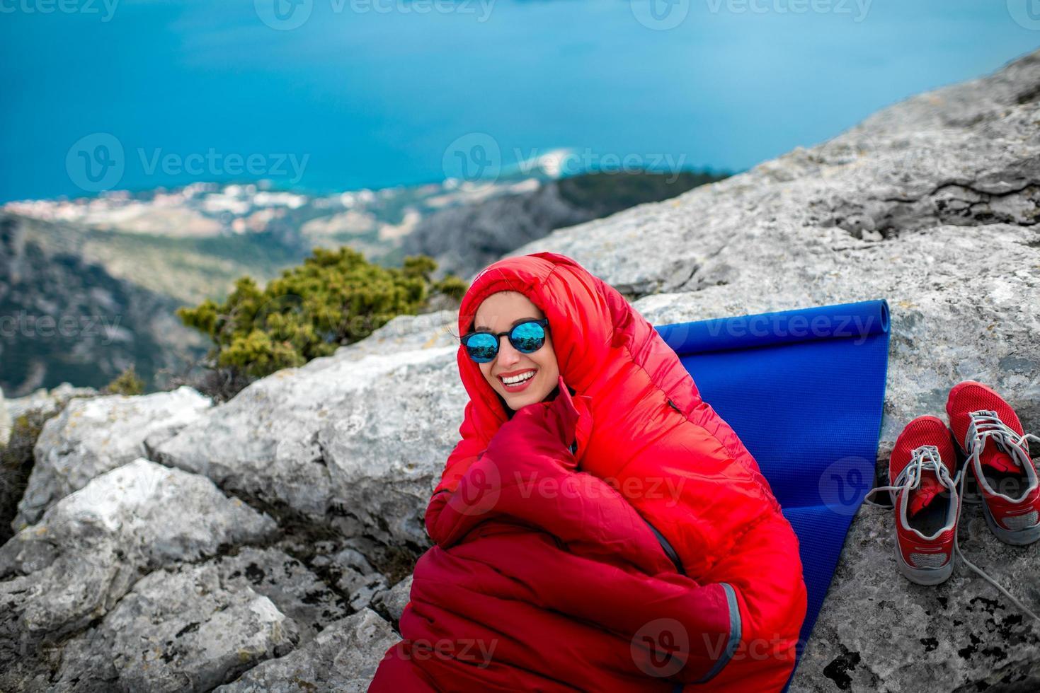 donna in sacco a pelo sulla montagna foto