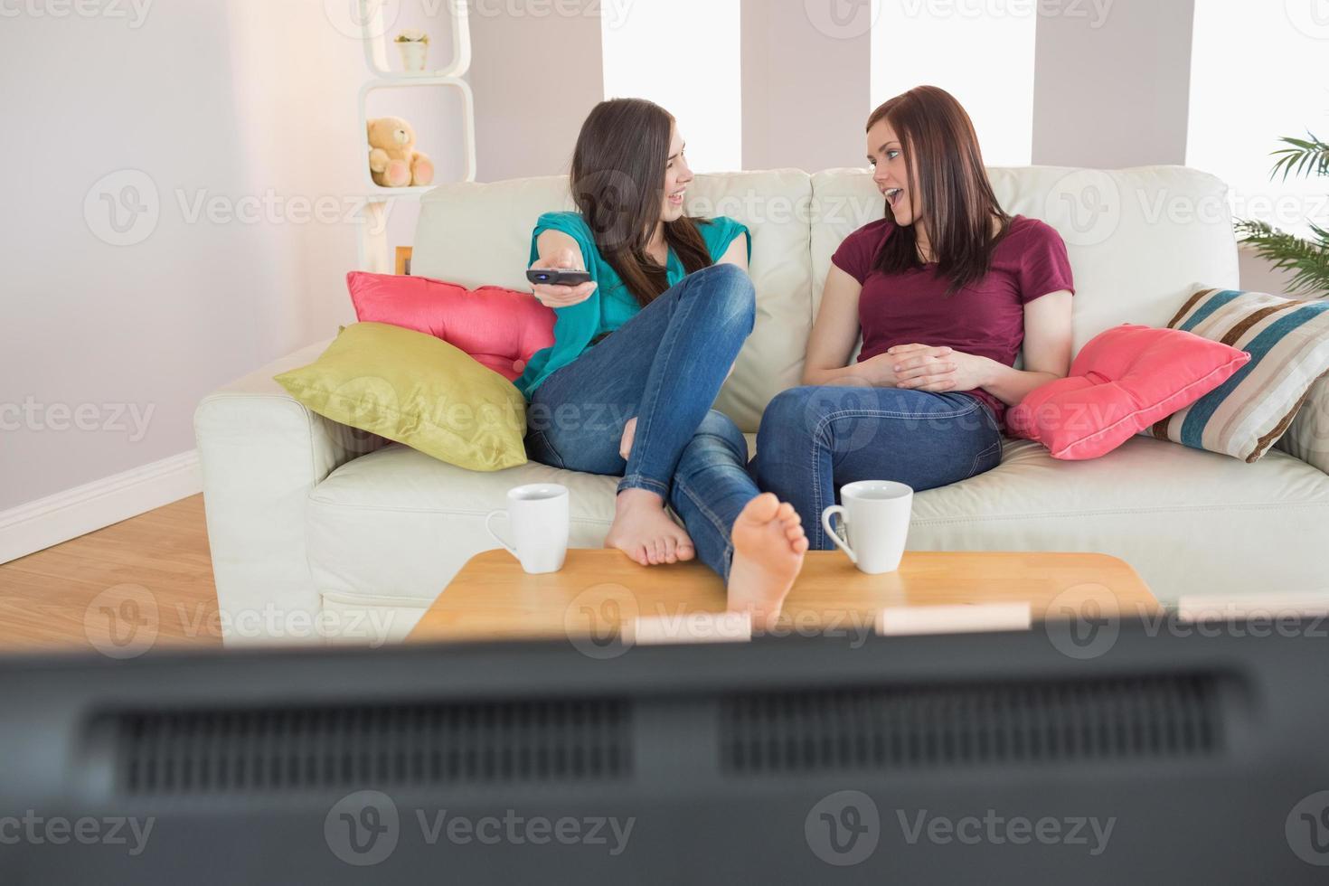 due amici felici sul divano a guardare la tv insieme foto