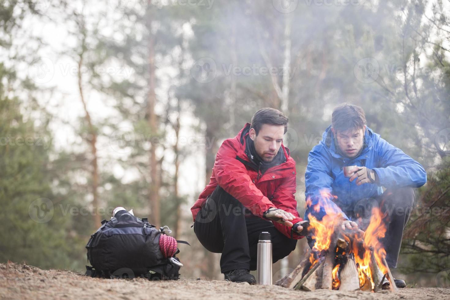 escursionisti maschi che si scaldano le mani al fuoco nella foresta foto