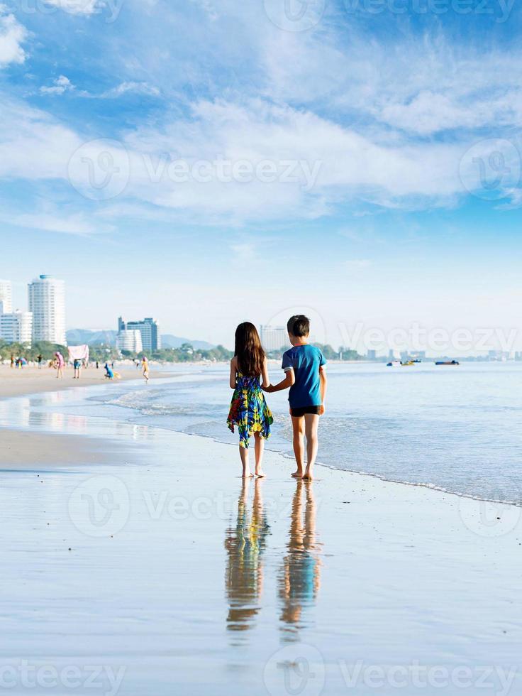 fratello sorella tenendo la mano a piedi sulla spiaggia foto