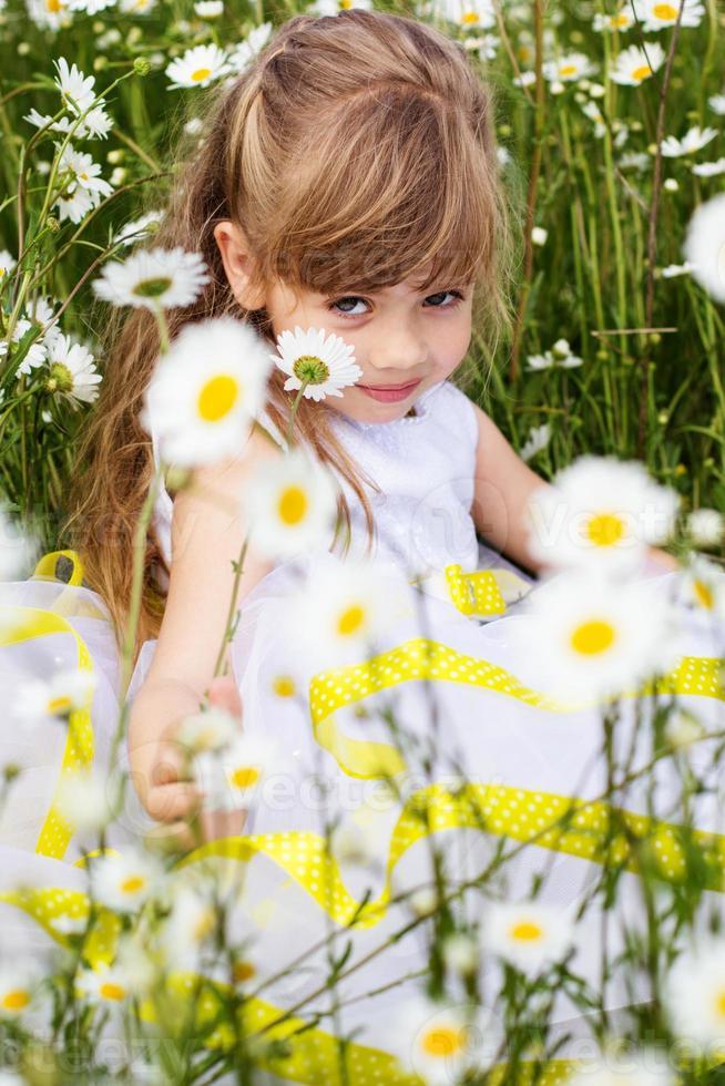 ragazza carina bambino al campo di camomilla foto