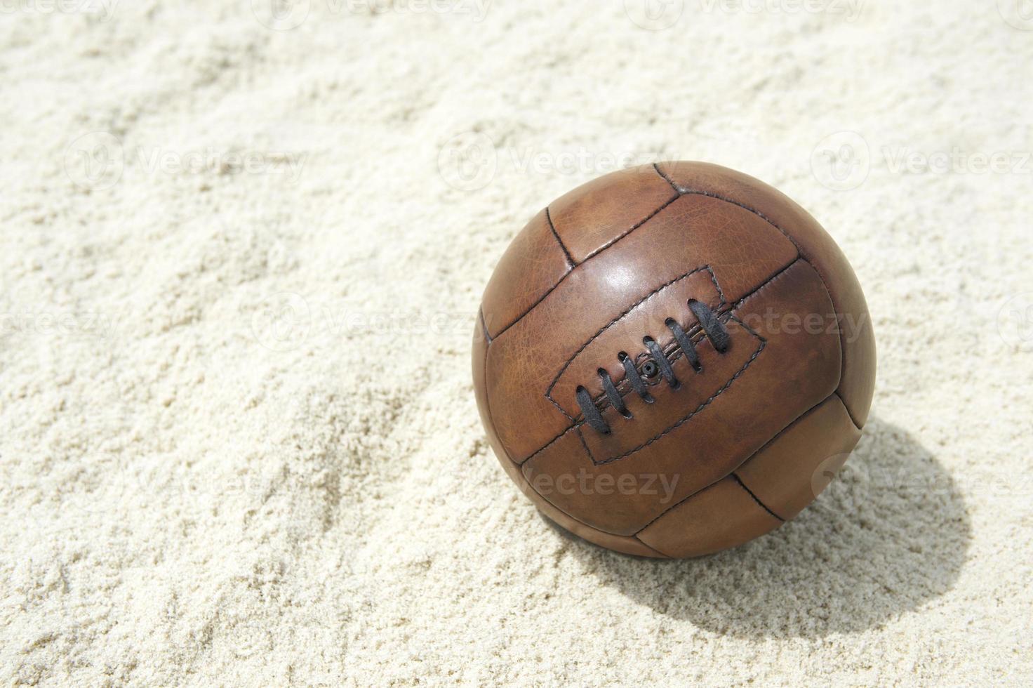 pallone da calcio marrone vintage calcio sfondo spiaggia di sabbia foto