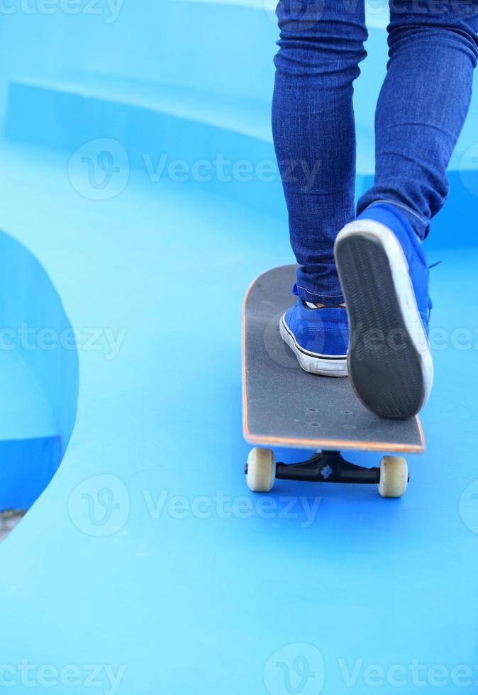 gambe in scarpe da ginnastica su skatepark foto
