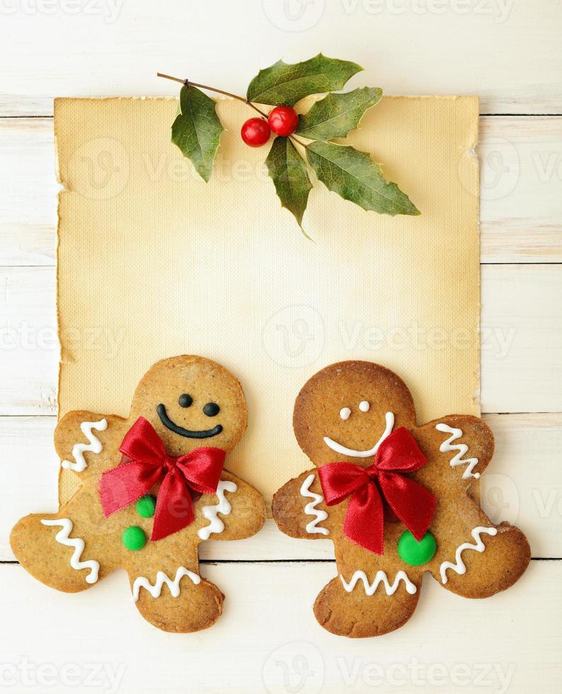 uomini di pan di zenzero sorridenti sul pezzo di pergamena con agrifoglio foto