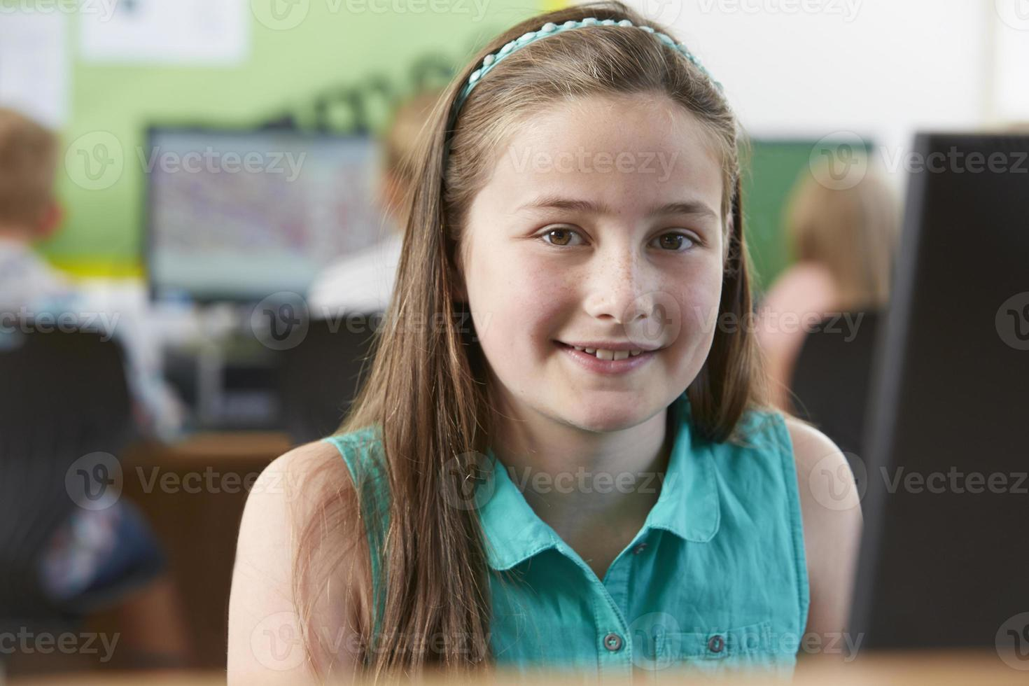 allievo femminile della scuola elementare nella classe del computer foto