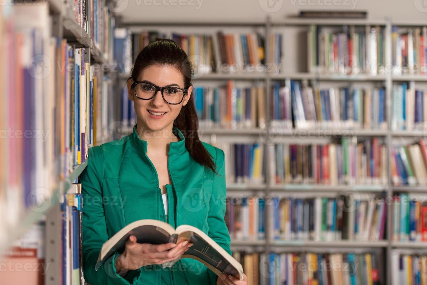 studentessa felice con il libro in biblioteca foto