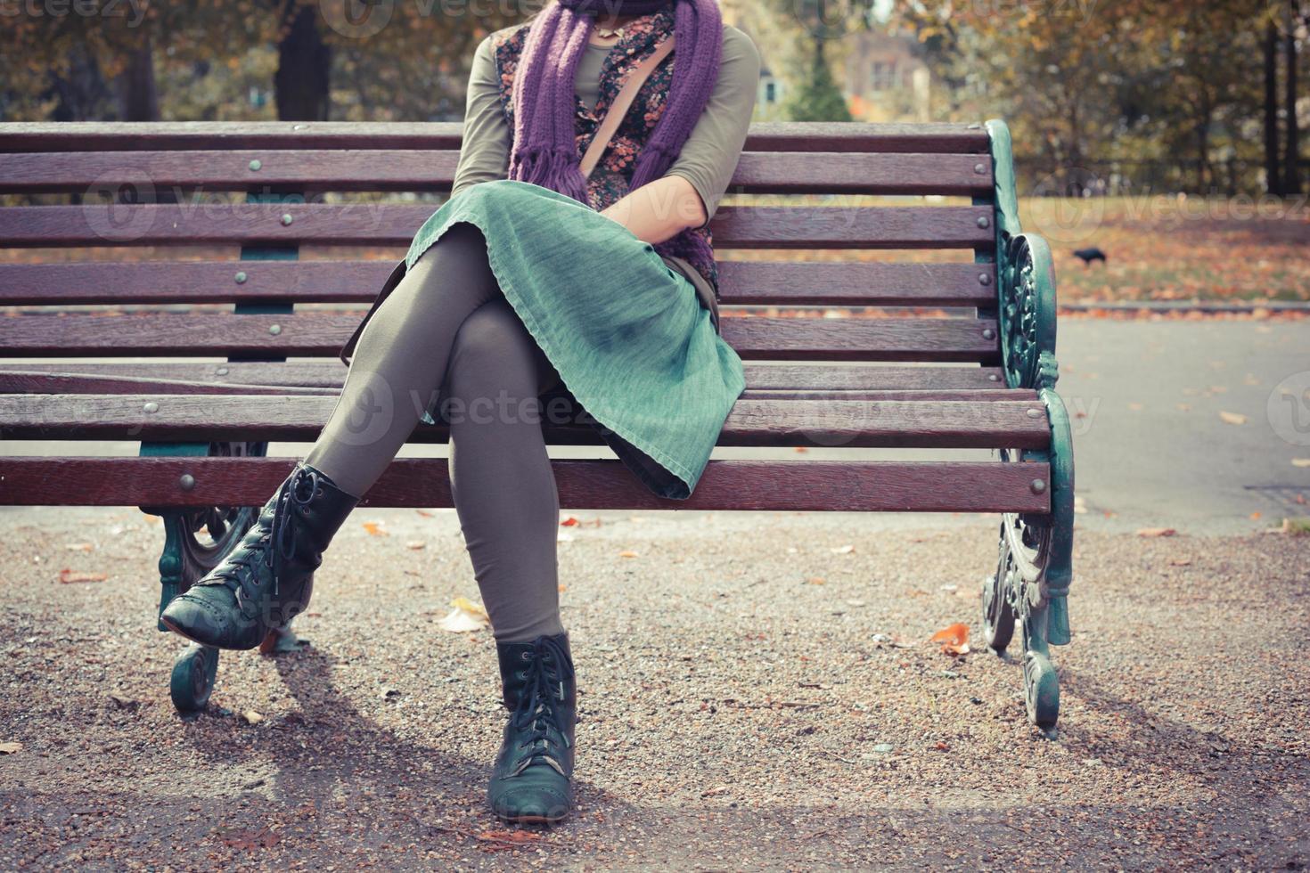 giovane donna seduta su una panchina foto