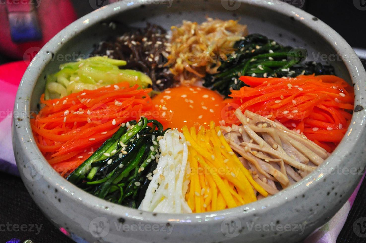 Bibimbap in una ciotola di pietra riscaldata, piatto coreano, da vicino foto
