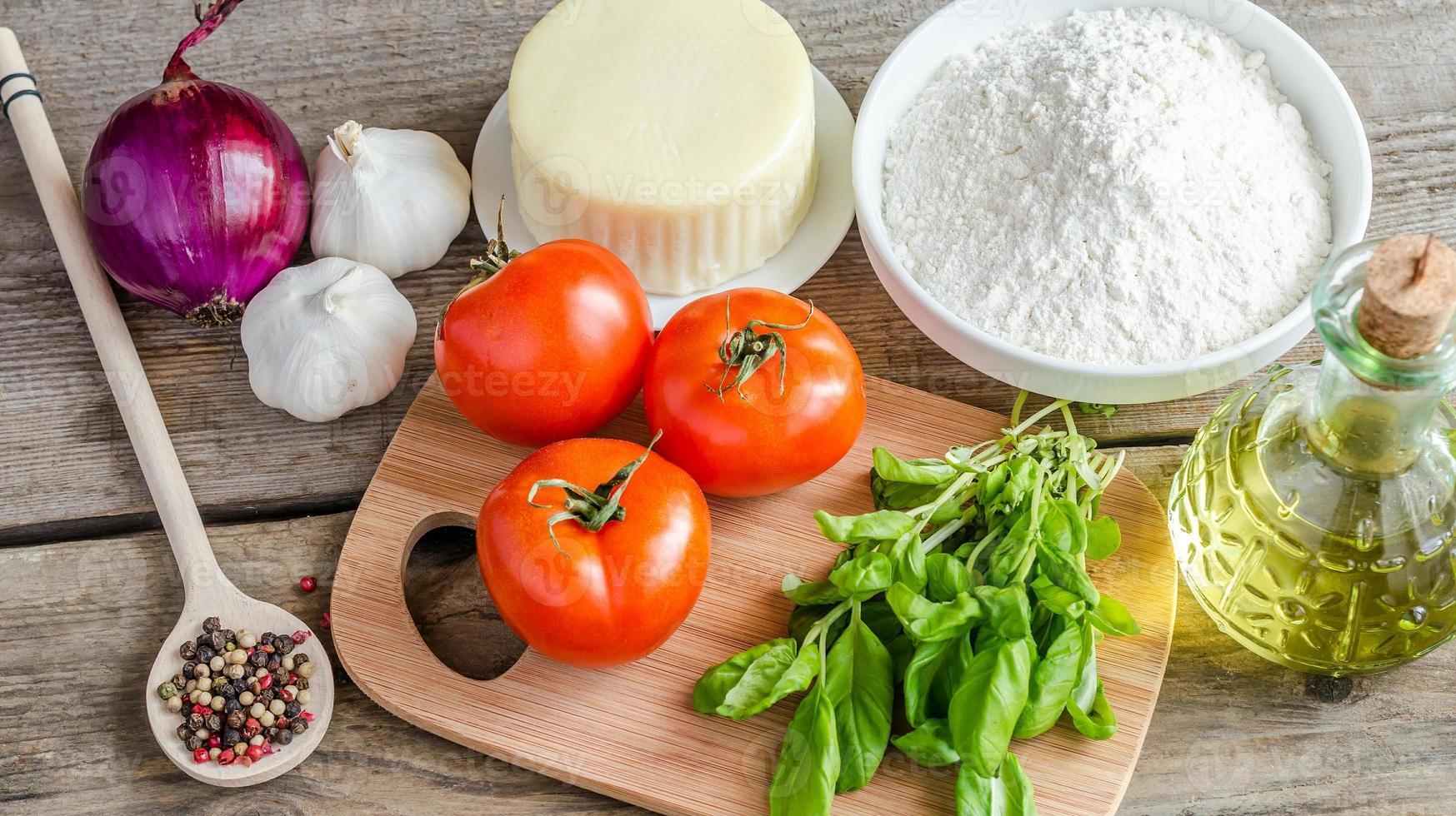 ingredienti per la pizza sullo sfondo in legno foto