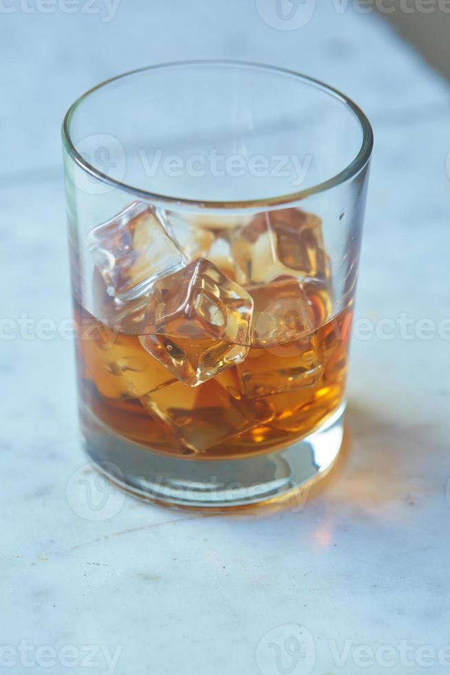 whisky con ghiaccio su un tavolo foto