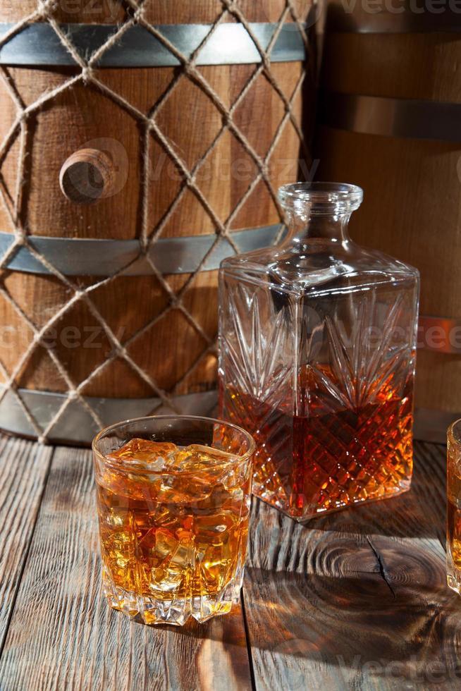 bicchiere di whisky con ghiaccio e decanter foto