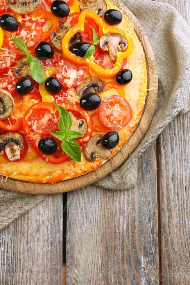 deliziosa pizza servita sul tavolo di legno foto